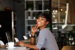 Mujer afroamericana sonriente que se sienta en el café con el ordenador portátil Foto de archivo