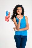Mujer afroamericana sonriente que sostiene la bandera de los E.E.U.U. y que mira para arriba Foto de archivo libre de regalías