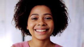 Mujer afroamericana sonriente que toca su pelo almacen de metraje de vídeo