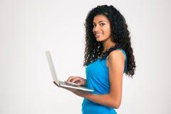 Mujer afroamericana sonriente que usa el ordenador portátil Imagenes de archivo