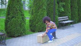 Mujer afroamericana torpe con un peinado afro que él camina abajo de la calle con una caja en su mano y que la cae almacen de video