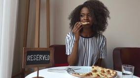 Mujer afroamericana vegeterian elegante fabulosa que come la pizza sin la carne en restaurante Almuerzo de asunto metrajes