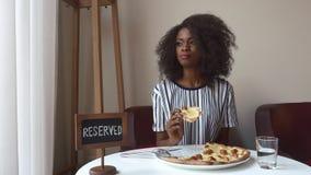 Mujer afroamericana vegeterian elegante que come la pizza sin la carne Almuerzo de negocios en restaurante metrajes