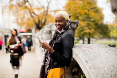 Mujer afroamericana y caucásica que presenta afuera con el móvil Foto de archivo libre de regalías