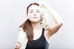Mujer agotada después de entrenar la cara de barrido con la toalla Fotografía de archivo libre de regalías