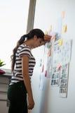 Mujer agotada por las notas pegajosas en oficina Imagen de archivo libre de regalías