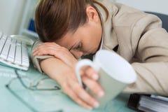 Mujer agotada que duerme en oficina después de día laborable duro fotos de archivo