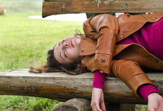 Mujer agotada que duerme en un banco de madera Fotografía de archivo libre de regalías