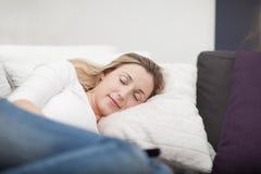 Mujer agotada que toma una siesta en el sofá Imagenes de archivo