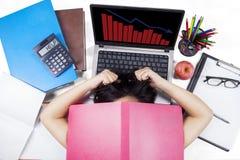 Mujer agotadora con el gráfico decreciente Foto de archivo