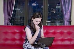 Mujer agotadora con un ordenador portátil en el apartamento Fotos de archivo libres de regalías
