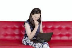 Mujer agotadora que trabaja con un ordenador portátil en estudio Fotos de archivo libres de regalías