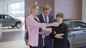 Mujer agradable en la chaqueta rosada que muestra la información en libro a los clientes La dependienta profesional ayuda al homb almacen de metraje de vídeo