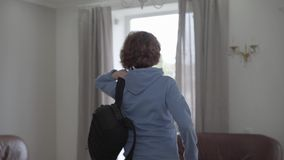 Mujer agradable madura puesta en la mochila cómoda en la parte posterior y el paseo dentro de la casa que sorprende almacen de metraje de vídeo