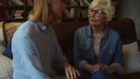 Mujer agradable que lee una revista de moda con su madre almacen de video