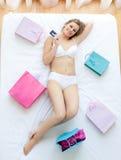 Mujer agradable que miente en cama con los bolsos de compras Imagen de archivo