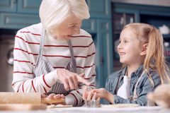 Mujer agradable que señala en la galleta en sus manos de las nietas Fotos de archivo