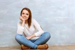 Mujer agradable que sienta a piernas cruzadas inclinarse en ella Fotos de archivo libres de regalías
