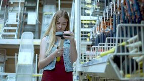 Mujer agradable que sostiene un martillo en una tienda almacen de video