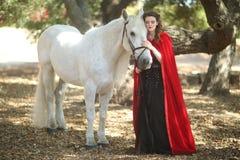 Mujer al aire libre con un caballo blanco Fotografía de archivo libre de regalías