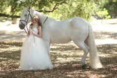 Mujer al aire libre con un caballo blanco Foto de archivo