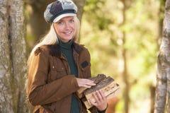 Mujer al aire libre en el arbolado del otoño que recolecta registros Fotografía de archivo libre de regalías