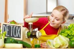 Mujer al lado de la máquina del juicer y de la muestra del detox fotos de archivo