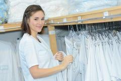 Mujer al lado de los uniformes lavados planchados estante Fotos de archivo libres de regalías