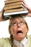 Mujer alarmada bajo la pila de libros en la pista Imagen de archivo libre de regalías