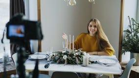 Mujer alegre atractiva que se sienta en el blog video de la grabación de la tabla sobre diseño de la decoración de la comida en c fotos de archivo libres de regalías