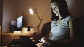 Mujer alegre atractiva que se sienta en el sofá y que tiene una llamada video con los amigos en la noche en casa Imagen de archivo libre de regalías