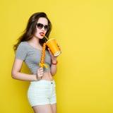 Mujer alegre caucásica atractiva con una taza de papel de jugo y Imagenes de archivo