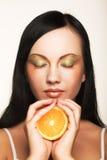 Mujer alegre con cercano anaranjado fresco su cara imagen de archivo libre de regalías