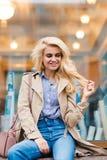 Mujer alegre con el pelo rubio de lujo que presenta mientras que se sienta cerca de la ventana de la tienda, hembra feliz con son Foto de archivo libre de regalías
