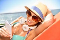 Mujer alegre con el smartphone que miente por la playa Imagenes de archivo
