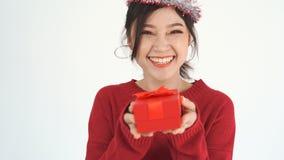 Mujer alegre con el sombrero y sostener una caja de regalo roja de la Navidad en un gesto del donante