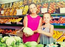 Mujer alegre con la col de compra de la muchacha en tienda de ultramarinos Imagen de archivo