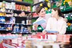 Mujer alegre con la hija que elige las galletas en supermercado Fotos de archivo