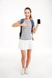 Mujer alegre con la mochila que señala el finger en el smartphone de la pantalla en blanco Fotos de archivo