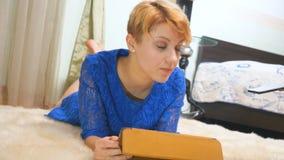 Mujer alegre con la tableta en la alfombra de la piel metrajes