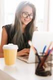 Mujer alegre con la taza de sentada del café y de ordenador portátil con Fotografía de archivo libre de regalías
