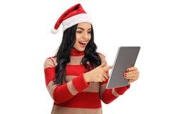 Mujer alegre con un sombrero de la Navidad que mira una tableta Imagen de archivo libre de regalías