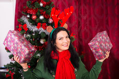 Mujer alegre de Navidad que muestra los regalos Imágenes de archivo libres de regalías