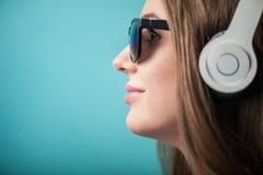Mujer alegre del inconformista con los auriculares y los vidrios Imágenes de archivo libres de regalías