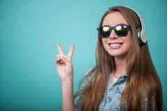 Mujer alegre del inconformista con los auriculares y los vidrios Foto de archivo