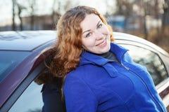 Mujer alegre del pelo rizado inclinada contra el coche Foto de archivo libre de regalías