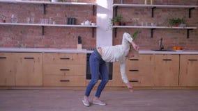 Mujer alegre deportiva que hace tirones gimnásticos en cocina en casa en la cámara lenta metrajes