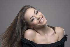 Mujer alegre despreocupada feliz con el pelo móvil del marrón del vuelo que sonríe y que mira la cámara Foto de archivo libre de regalías