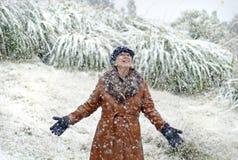 Mujer alegre emocionada que se coloca en la nieve que cae por la primera vez en vida Imagenes de archivo