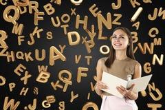 Mujer alegre en el beige con un cuaderno, letras Imagenes de archivo